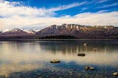 Insel im alpinen See mit Bergen Stockbilder