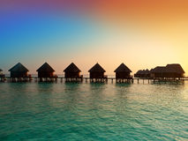 Insel im Ozean, der Landhäuser Sonnenuntergang zu der Zeit. Stockfotografie