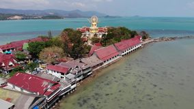 Insel mit buddhistischem Tempel und vielen Häusern Vogelperspektive von Insel mit buddhistischem Tempel mit Statue großer Buddha stock video