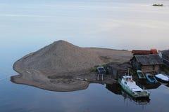 Insel mit einem Berg des Kieses unter dem Fluss und festgemachte Boote und Boote stockfotos