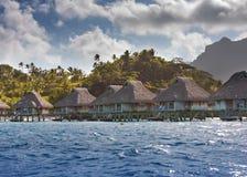 Insel mit Palmen und kleinen Häusern auf Wasser im Ozean und Berge auf einem Hintergrund Stockfotos