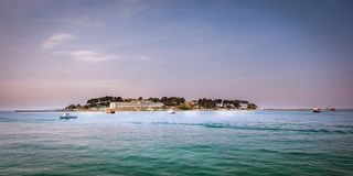 Insel Sveti Nikola nahe Porec, Kroatien mit Hotelerholungsort und Booten in der Front stockfotos