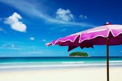 Insel und Regenschirm lizenzfreie stockbilder