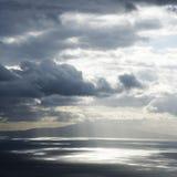 Insel und Sonne durch Wolken. Lizenzfreies Stockfoto