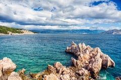 Inselklippen und -wellen im Ozean, gesehen von der Küstenlinie Ruhiges Wasser, klarer Himmel und Wellen an einem sonnigen Sommert Lizenzfreies Stockbild