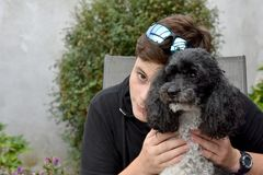 Best friends, teenage boy and his harlequin poodle royalty free stock photos