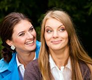 We are inseparable lovely girlfriends. Two inseparable cheerful girlfriends looking at someone in summer park Royalty Free Stock Photography