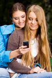 We are inseparable lovely girlfriends. Two inseparable cheerful girlfriends with mobile phone in summer park Royalty Free Stock Photos
