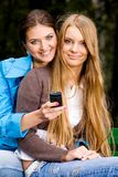 We are inseparable lovely girlfriends. Two inseparable cheerful girlfriends with mobile phone in summer park Stock Photos