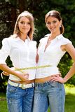 We are inseparable lovely girlfriends. Two inseparable cheerful girlfriends measuring waist in summer park Royalty Free Stock Photography