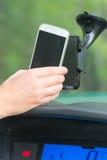 Inserción del teléfono elegante en el soporte para coche Imágenes de archivo libres de regalías