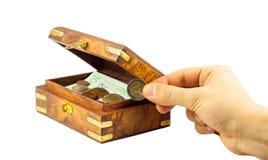 Inserendo una moneta nel contenitore di monili Immagini Stock
