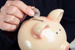 Inserendo una moneta in un porcellino salvadanaio Fotografie Stock Libere da Diritti