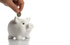 Inserisca la moneta in un porcellino salvadanaio felice Immagini Stock Libere da Diritti