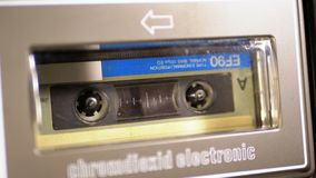 Insert an Audio Cassette into a Tape Player and Playback. Vintage Cassette recorder plays the tape inserted therein. Close up. Retro Tape with a blank label in stock footage