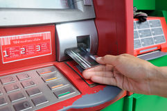Insert card into an ATM to begin a financial transaction. Inserting card into an ATM to begin a financial transaction Royalty Free Stock Photography