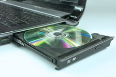Insert a CD into the laptop stock photos