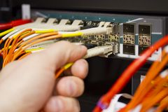 Insert Fiber Cable. Insert a fiber cable into a switch in datacenter stock photo