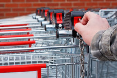 Insert money Supermarket shopping cart. Inserting coin or token into shopping cart at the superstore Royalty Free Stock Image