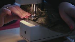 Inserte la aguja de la máquina de coser en la tela y haga una línea 4k, 3840x2160 almacen de metraje de vídeo