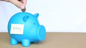 Inserte las monedas en la hucha azul con la nota y la palabra pegajosas de la boda en el concepto de dinero del ahorro para casar metrajes