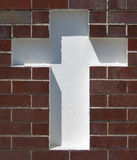 Inserted White Cross. White cross inserted in a brick wall Royalty Free Stock Photos
