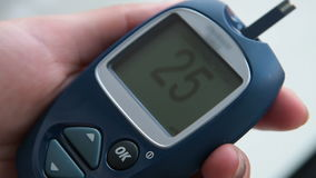 Inserting blood test strip into the glucometer stock video
