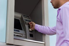 Inserting card into cash dispenser. Handsome young man inserting card into cash dispenser Royalty Free Stock Images