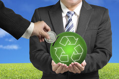 Inserting coin into ball with recycling symbol with nature backg. Hand hold coin insert into ball with recycling symbol with green meadow and blue sky background Stock Photos