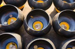 Inserting a coin into the bowl Belief in Buddhism. Royalty Free Stock Photography