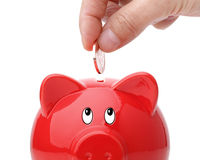 Inserting coin into a piggy bank Royalty Free Stock Images