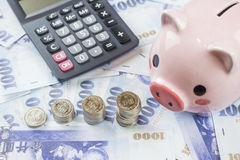 Inserting a coin into a piggy bank Royalty Free Stock Photography
