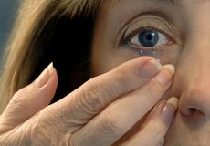 Inserting Contact Lens. A woman inserting a contact lens in her eye Royalty Free Stock Image