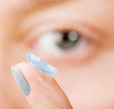 Inserting a contact lens in female eye Stock Photos