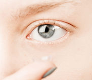 Inserting a contact lens in female eye Royalty Free Stock Photo