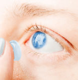 Inserting a contact lens in female eye Stock Image