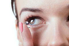 Inserting a contact lens in female eye Stock Images
