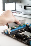 Inserting DDR 3 memory in the socket Stock Photos