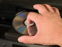 Inserting dvd disk in player. Arm inserting dvd blu-ray disk in the audio hi-fi player Stock Images