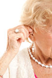 Inserting Hearing Aid. Closeup of a senior woman's hand inserting a hearing aid in her hear royalty free stock photography