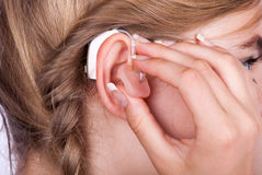 Inserting a hearing aid Royalty Free Stock Photos