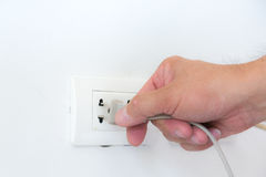Inserting plug in outlet. Stock Photo