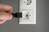 Inserting plug in outlet. Male hand trying to plug an american type of plug to an internet outlet stock photography