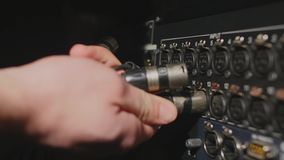 Inserting professional XLR audio cables to the rear panel of the professional recorder Stock Images