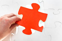 Inserting red puzzle piece on free space Stock Photo
