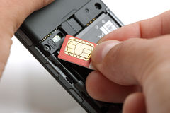 Inserting a sim card. Into the back of a mobile phone Stock Photos