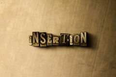 INSERTION - close-up of grungy vintage typeset word on metal backdrop Royalty Free Stock Photos