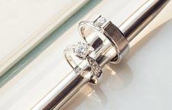 insertion de baguette en métal à moins de deux anneaux de noces de diamant pour le marié et la jeune mariée sur le fond blanc Photo stock