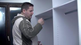 Insertion des tiges de cintre de cabinet banque de vidéos