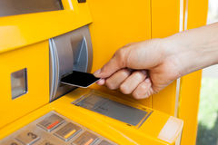 Inserts a plastic card into the ATM Stock Image